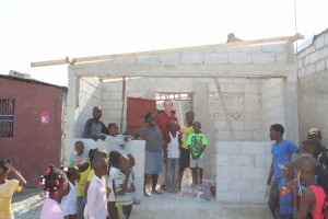 HOME-2-in-Cite-Soleil-Ken-standing-with-mother-and-children-roof-was-under-construction-but-now-finished